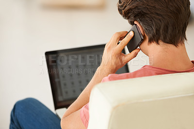 Buy stock photo Rear-view of a young man talking on his mobile while using his laptop