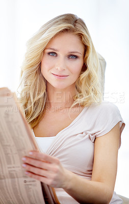 Buy stock photo Portrait of a pretty young blond woman reading the newspaper at home