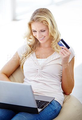 Buy stock photo Young woman relaxed at home as she shops online