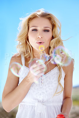 Buy stock photo Pretty young woman blowing bubbles right at you