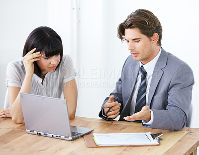 Buy stock photo Two young executives having a meeting at the office together