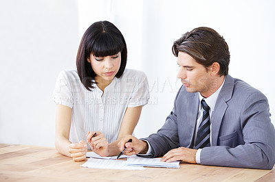 Buy stock photo Two young executives going over a project budget together