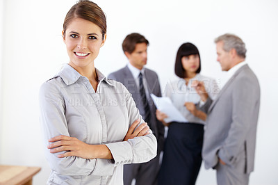 Buy stock photo Portrait of a pretty young executive with her team standing in the background