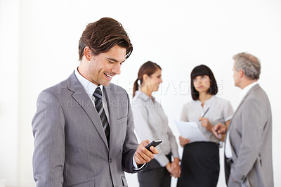 Buy stock photo A young handsome executive looking at his smartphone while his team stands in the background