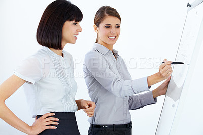 Buy stock photo Two beautiful young executives working on a whiteboard together