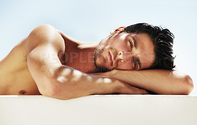 Buy stock photo Portrait of a sexy male resting his head on his arms lying down horizontally