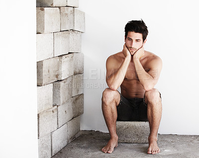 Buy stock photo A lonely looking young male sitting on a brick in a corner wearing a pair of shorts - Copyspace