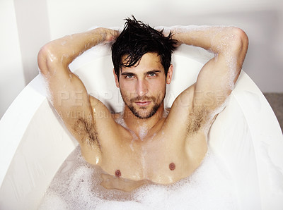 Buy stock photo Sexy portrait of a young handsome male relaxing in a bath tub of bubble bath