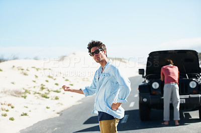 Buy stock photo A young man trying to hitch a ride while his friend looks at the engine in the background