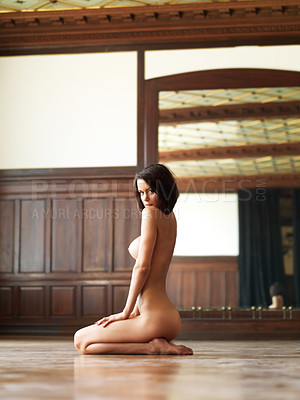 Buy stock photo Sexy nude woman kneeling in a room, looking seductively over her shoulder at you