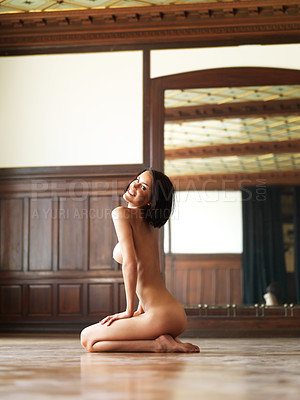 Buy stock photo Sexy nude woman kneeling in a room, smiling over her shoulder at you