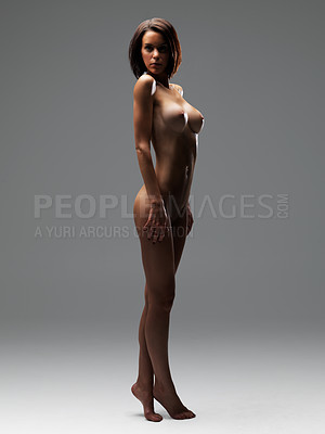 Buy stock photo Full-length image of a nude woman standing against a plain background with accentuating shadows