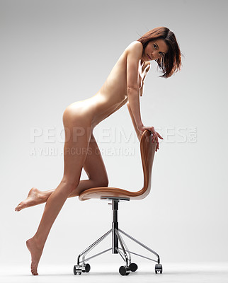 Buy stock photo Beautiful nude young woman standing next to a chair - isolated