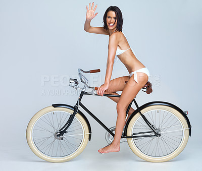 Buy stock photo Bikini-clad young woman riding a bicycle isolated on grey