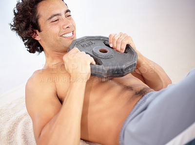 Buy stock photo A sexy young man doing situps with a weight on the floor