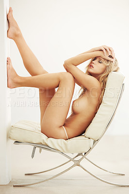 Buy stock photo Shot of a gorgeous young topless woman reclining in a designer chair
