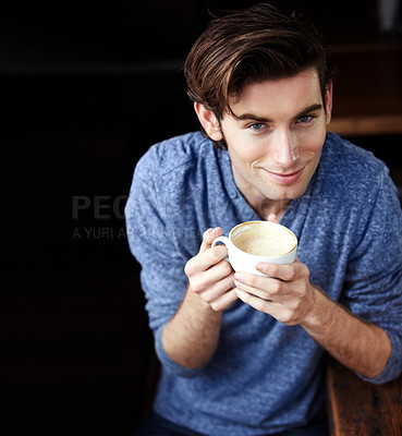 Buy stock photo A young man standing, looking upwards with coffee in hand