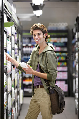 Buy stock photo A young man picking up some groceries at the store