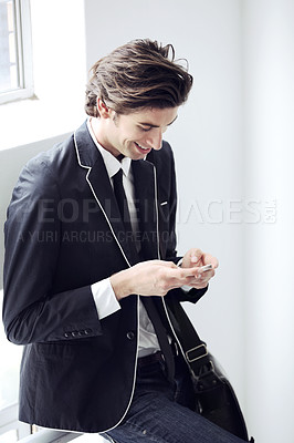 Buy stock photo A young man typing a message on his cellphone