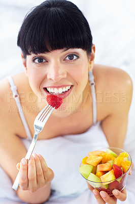 Buy stock photo Lovely young woman enjoying a fruit salad while lying in bed