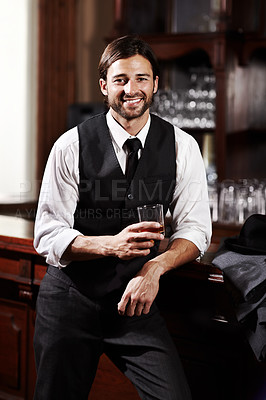 Buy stock photo Portrait of a well-dressed young man standing at a bar with a drink