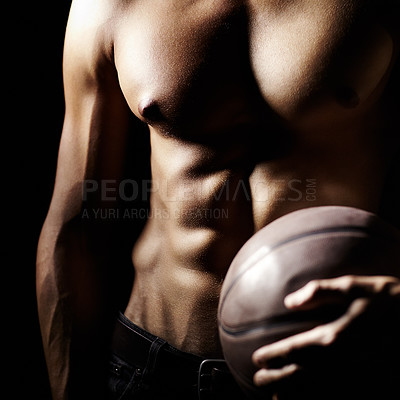Buy stock photo Cropped image of a muscular young man holding a basketball