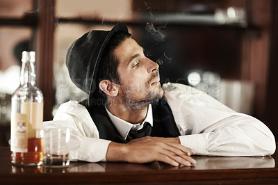 Buy stock photo A handsome young bartender smoking with a bottle of whiskey next to him