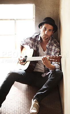 Buy stock photo A handsome young musician playing a guitar