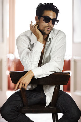 Buy stock photo A handsome young man wearing sunglasses and sitting on a chair