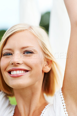 Buy stock photo Happy young woman holding up a piece of white linen