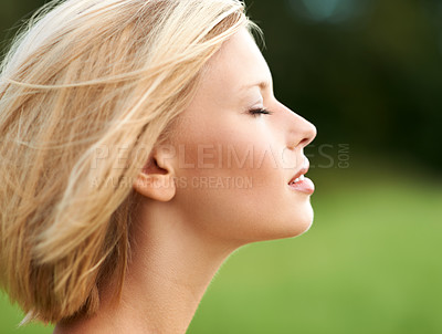 Buy stock photo Attractive young woman savoring the breeze outdoors - profile
