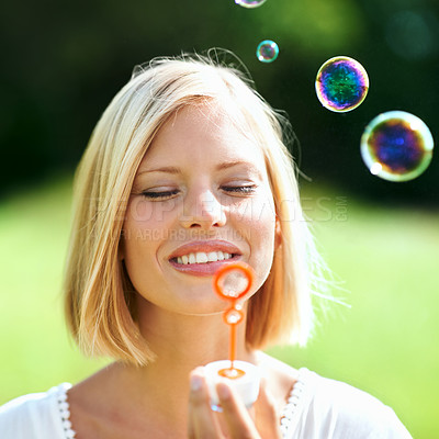 Buy stock photo Smiling young woman blowing soap bubbles outdoors