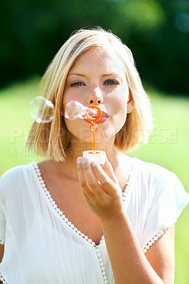 Buy stock photo Lovely young woman blowing soap bubbles outdoors