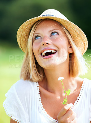 Buy stock photo Happy young woman wearing a hat and smiling while holding a tiny flower