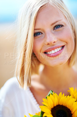 Buy stock photo Smiling young woman holding some sunflowers while outdoors