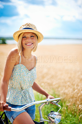 Buy stock photo Pretty young woman standing with her bicycle in the countryside