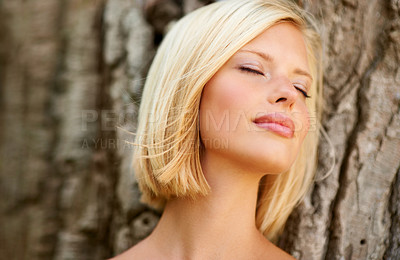 Buy stock photo Relaxed young woman leaning against a tree trunk