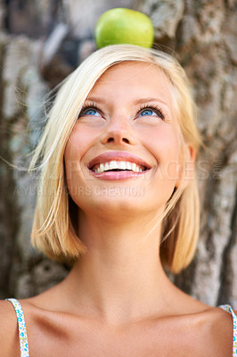 Buy stock photo Smiling young woman leaning against a tree trunk with an apple balanced on her head