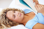 Closeup of a young woman lying on bed reading book