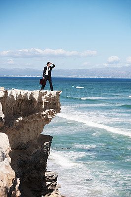Buy stock photo Businessman standing on a cliff overlooking the ocean and searching the horizon