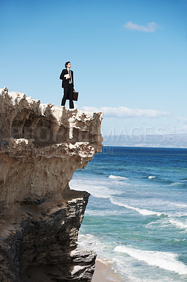 Buy stock photo Young businessman holding a briefcase and a book standing on the edge of a cliff overlooking the ocean
