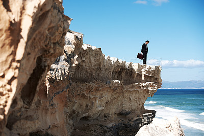 Buy stock photo Businessman holding a briefcase standing on a cliff looking down towards the ocean
