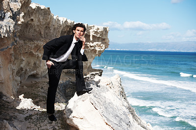 Buy stock photo Handsome businessman posing for the camera on a rock overlooking the ocean