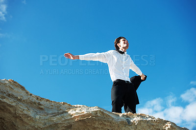 Buy stock photo Low-angle view of happy businessman standing on a rock with his arms outstretched