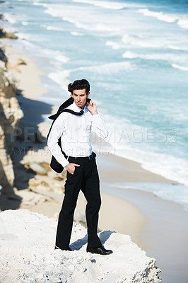Buy stock photo Handsome businessman standing on a cliff above the ocean with his jacket tossed over his shoulder