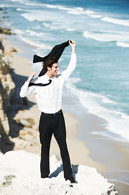 Buy stock photo Handsome businessman standing on a cliff above the ocean waving his jacket in the air