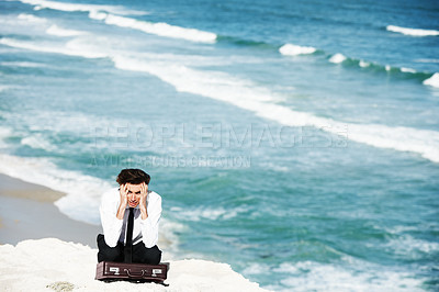 Buy stock photo Young businessman sitting on a cliff above the ocean with his hands in his hair