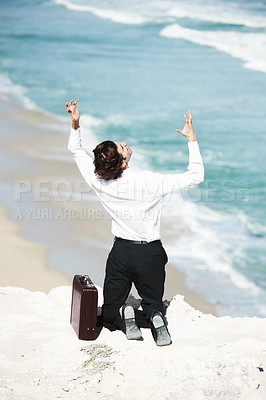 Buy stock photo Businessman kneeling on a cliff overlooking the ocean with his hands in the air