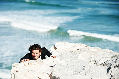 Buy stock photo Businessman clambering up the side of a cliff overlooking the ocean