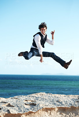 Buy stock photo Happy young man jumping in the air with the ocean in the background